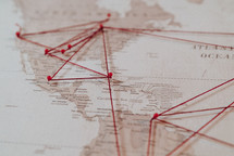 push-pins and string on a world map