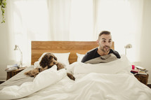 Suprised man sitting up in bed with dog.