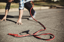 Jumper cables attached to man bent down with hands on street in running position.