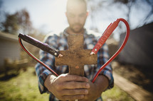 Man holding clay cross with jumper cables attached.