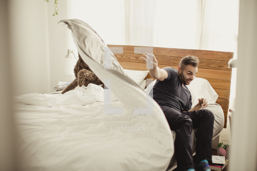 Man rising from bed, throwing comforter on dog in bed.