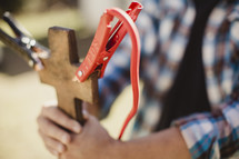 Hands holding wooden cross with jumper cables attached.
