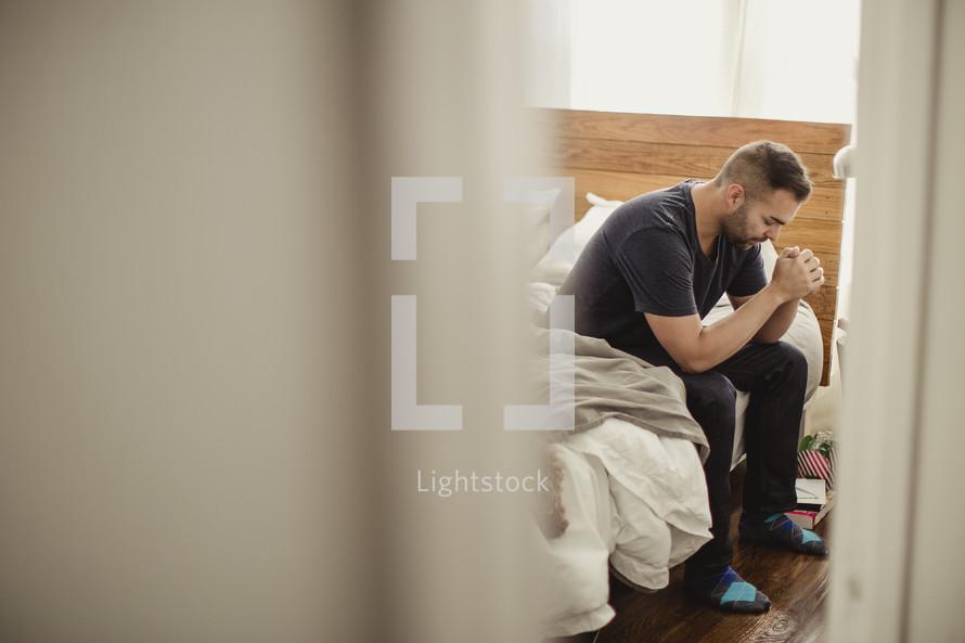 Man sitting on side of bed praying.