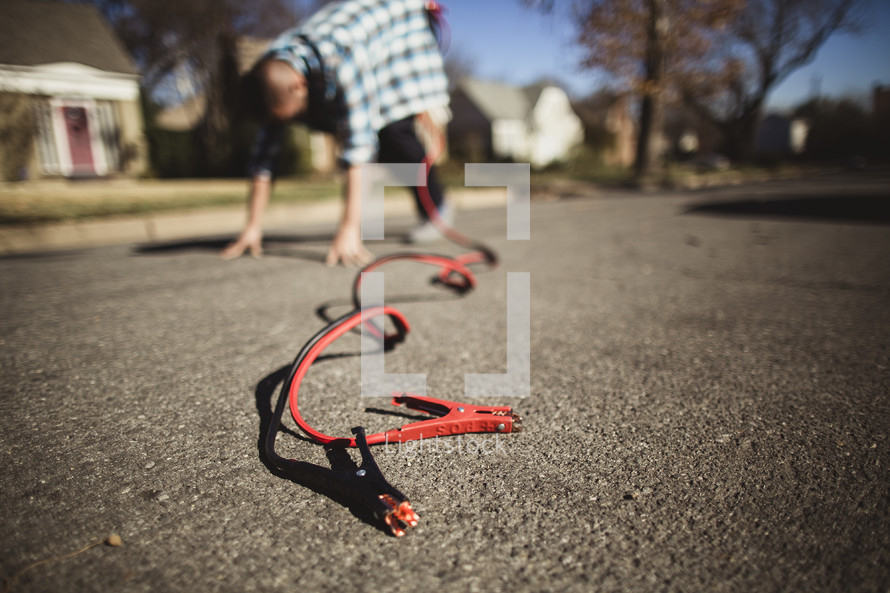 Jumper cables attached to man bending over in the street.