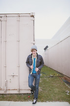 man in hat and jacket standing in front of a storage locker