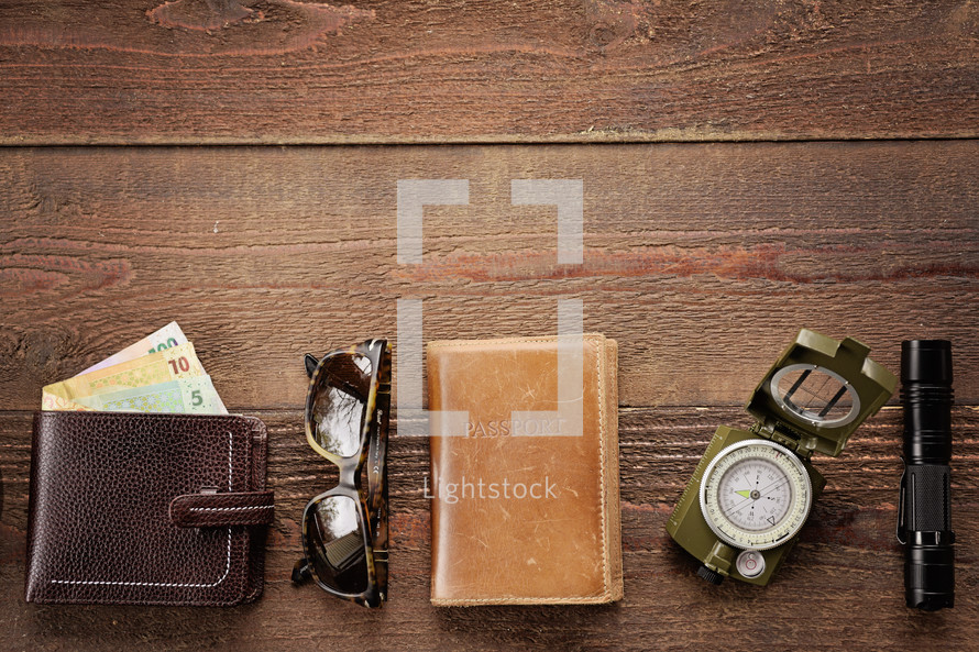 riyals, wallet, sunglasses, passport, compass, and flashlight