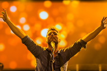 A man at a microphone with arms raised worship leader passion singing