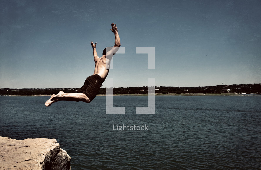 Man jumping off rock into the lake