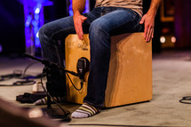 Man in socks sitting on cajon wooden drum box on stage playing hitting percussion
