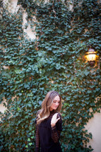 a woman posing in front of an ivy covered wall