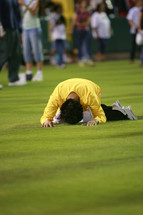Man prone on face praying bowing before god on grass field crusade salvation.