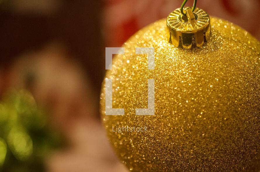 Gold glitter ball ornament hanging on Christmas tree.