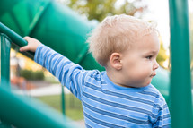 a toddler boy on playground equipment