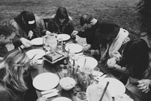 prayer at a fall dinner party outdoors