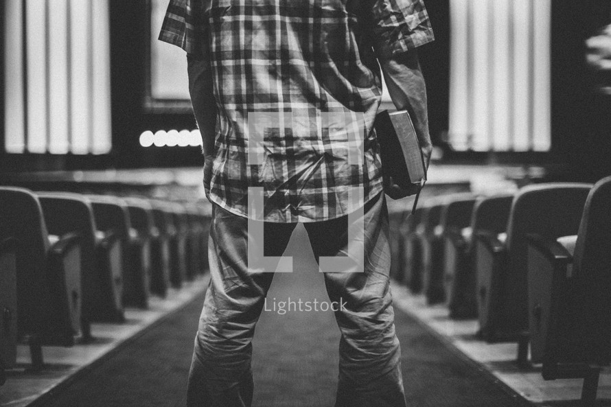 man standing in the center of a church aisle holding a Bible