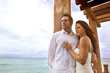 A bride and groom standing near the ocean
