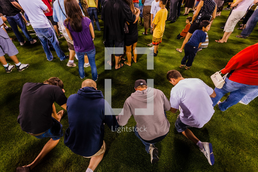 Young men in prayer holding hands crusade accept Christ salvation kneeling one knee