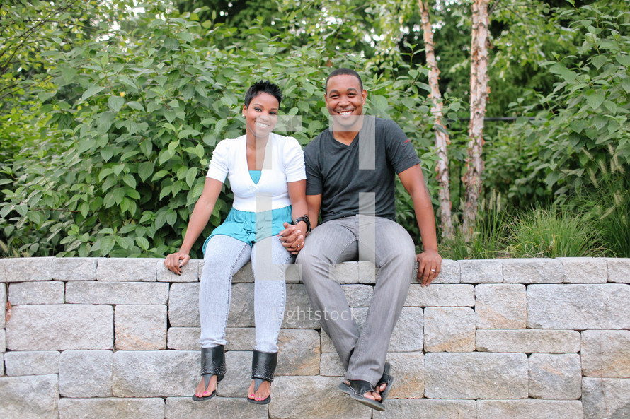 couple sitting on a stone wall holding hands