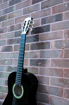 black acoustic guitar against a brick wall