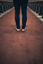 woman standing in the center of an aisle of a church