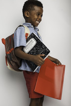 a boy child holding school supplies