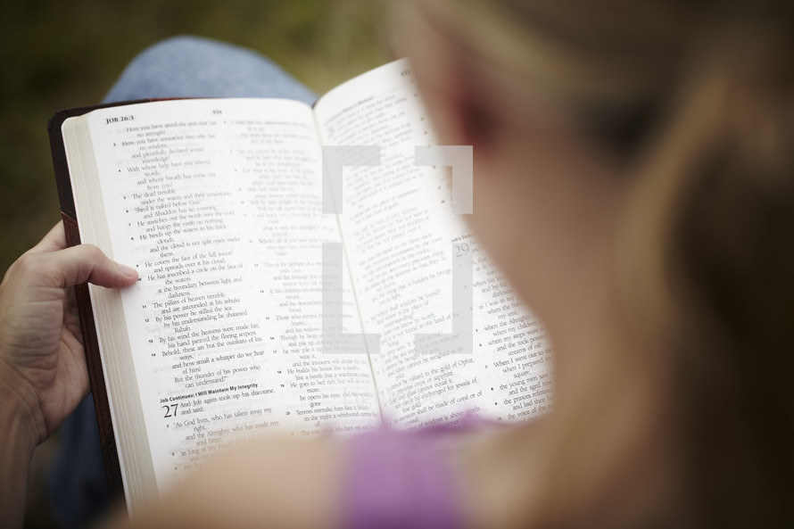 An over the shoulder view of a woman reading her Bible
