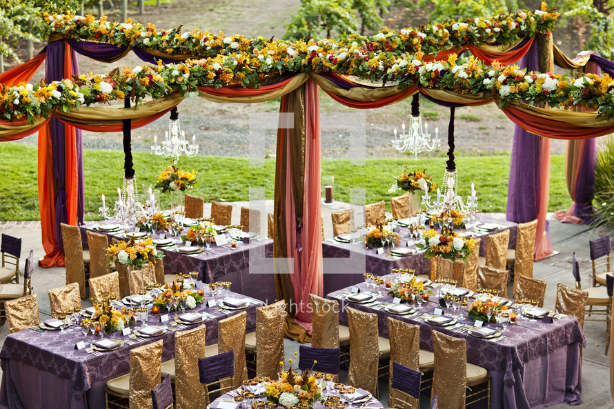 ornately decorated tables at a wedding reception, gold, purple wedding design , floral drapes chairs linens dinner