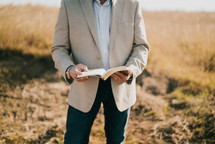 a man standing outdoors holding a Bible