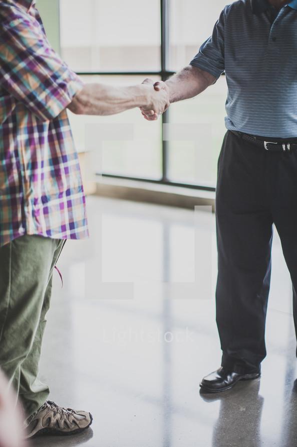 men shaking hands at a church entrance