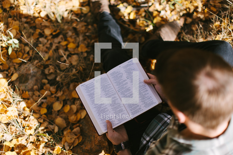 man sitting in fall leaves reading a Bible