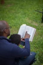 A father reading the Bible with his young son in the back yard.