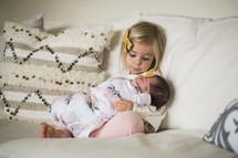 big sister holding a newborn