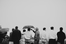 tourists standing under umbrellas