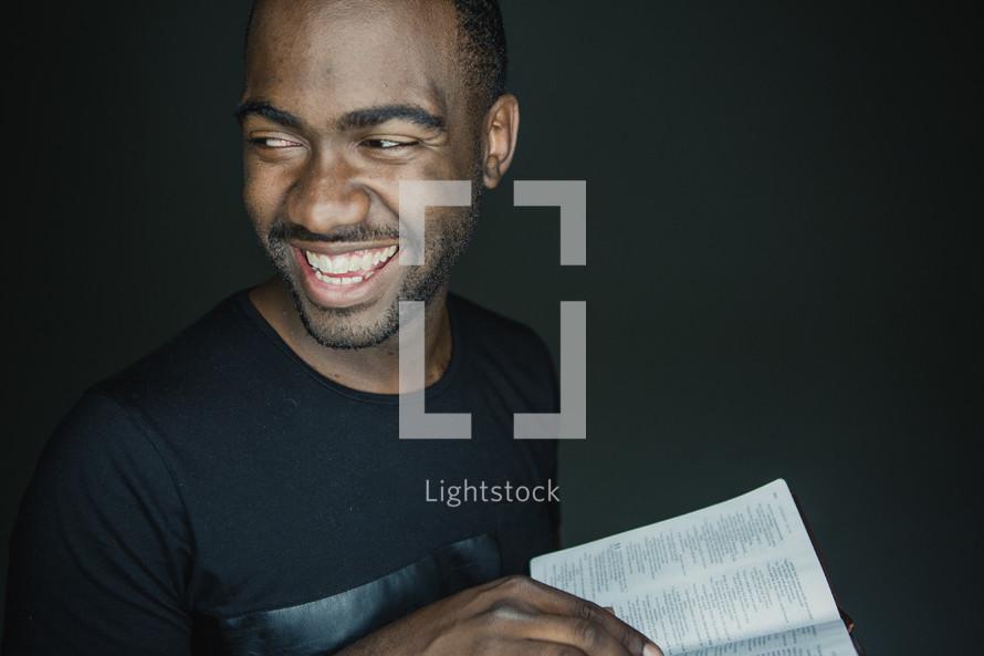 man smiling holding an open Bible