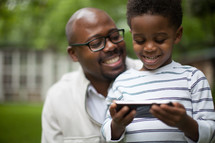 father and son looking at a cellphone screen