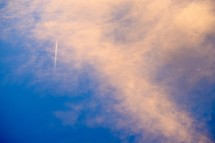 plane contrails and pink clouds in the sky at sunset