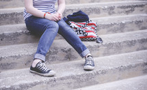teen sitting on concrete steps