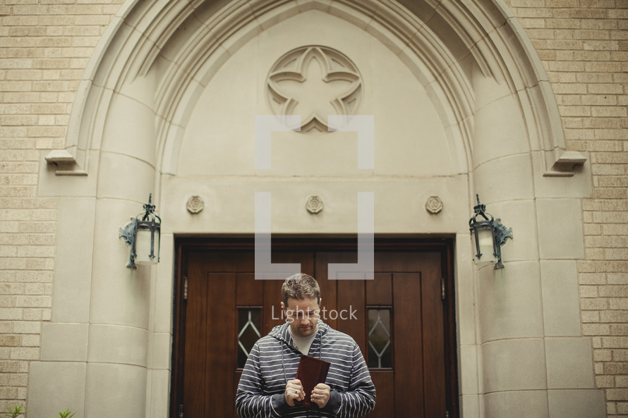 man holding a bible in front of church doors