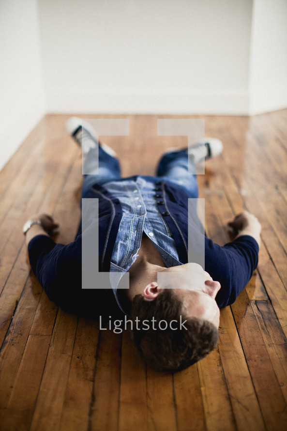 man lying on a wood floor