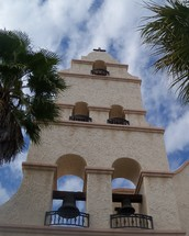 This church bell tower reaches high in the sky towering above a city square reaching high into the Heavens showing the light of the world to all who pass by. This church is a new church building designed after the old spanish style missions out west.