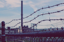 barbed wire at the top of a fence at a prison