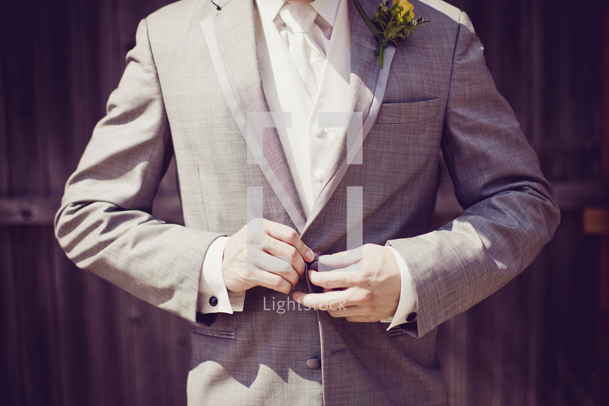 A groom buttons his grey jacket.