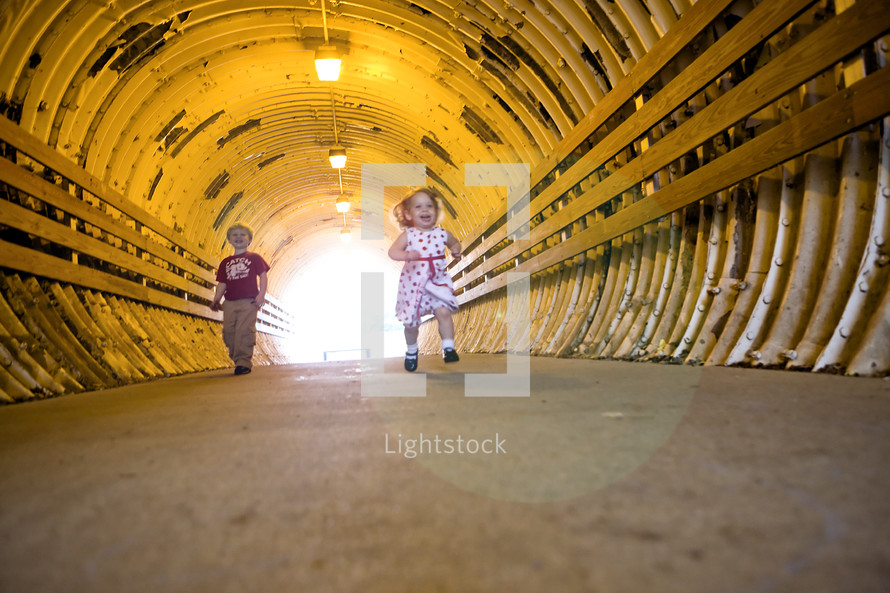 toddler boy and girl running in a tunnel