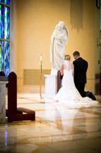 bride and groom - kneeling at altar, prayer - church interior