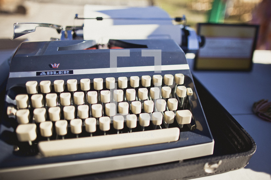 A traveling typewriter with a piece of paper attached