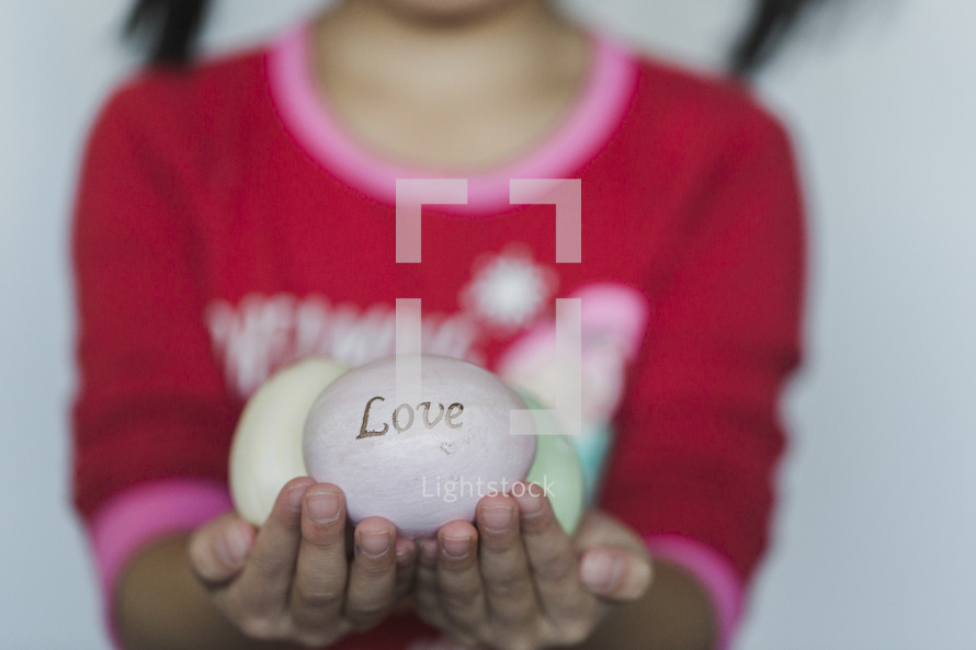 kid holding faith, hope, and love Easter eggs