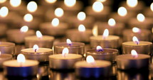 Dolly shot of many candles burning with shallow depth of field. 4k