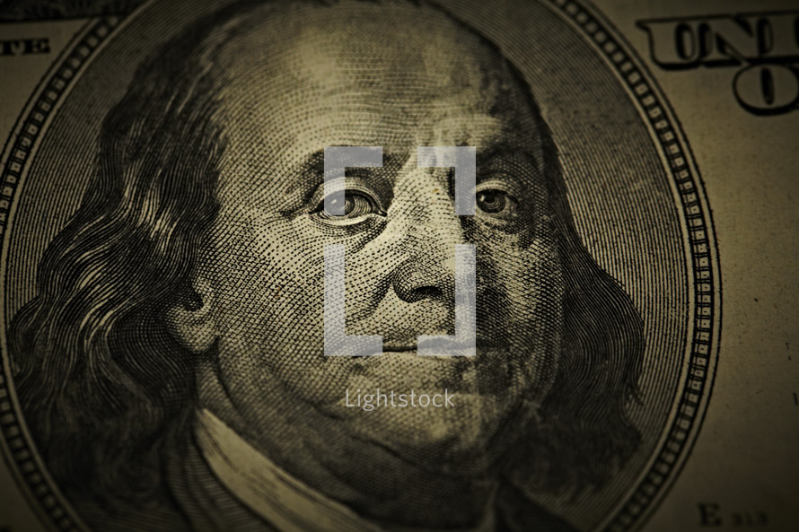 Close up of Benjamin Franklin's face on a one hundred dollar bill
