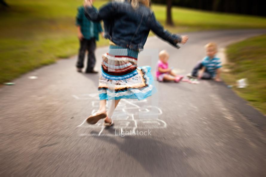 girl playing hop scotch