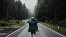 a man in a rain coat standing in the middle of a rural road